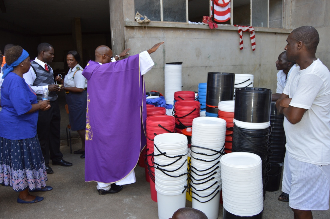 Fr. Kunaka blesses the buckets and slippers donated to Chikurubi Prisoners.JPG