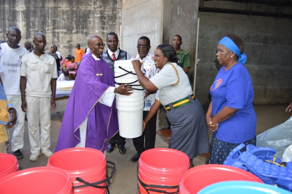 Its all smiles as Fr. Kunaka hands over donated items to (P.O.C.W) Mrs. Mutasa.JPG