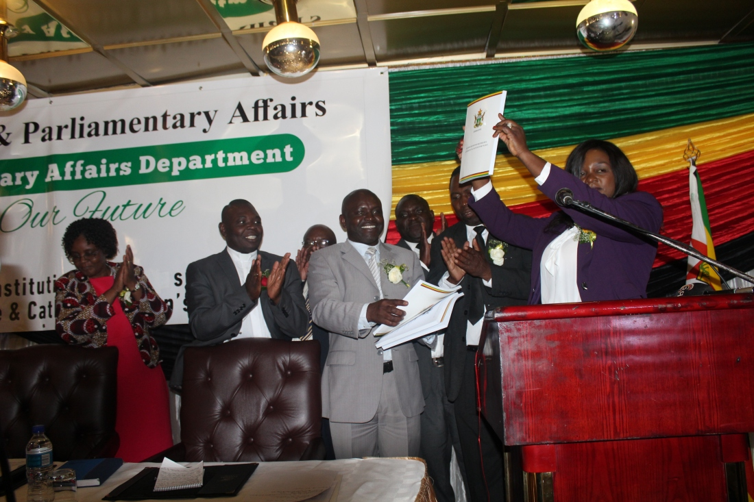 Mrs V. Mabiza shows a copy of the translated version of the constitution while Bishop Nyandoro (clapping) looks on..JPG