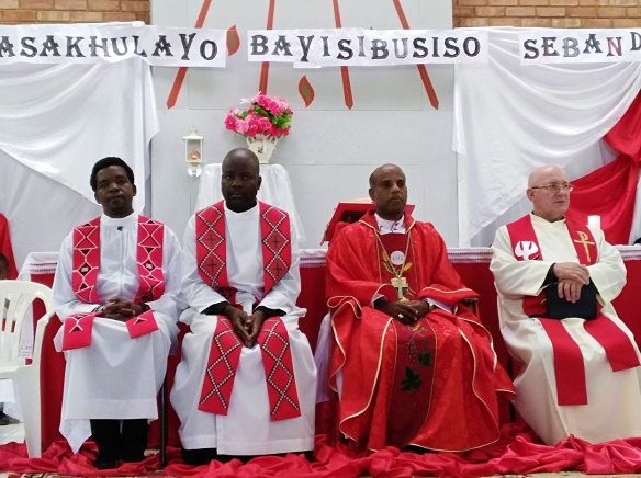 Archbishop Alex flanked by priests durind celebration of the feast of Pentecost at Holy Spirit parish in Bulawayo.