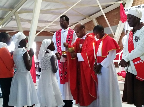 Catechumens receive holy communion from Archbishop Alex..jpg