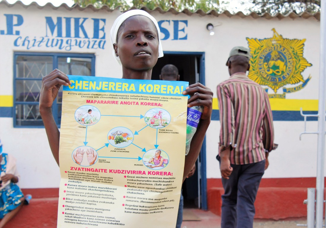 A woman displays a banner encouraging people to fight against cholera in Chitungwiza.
