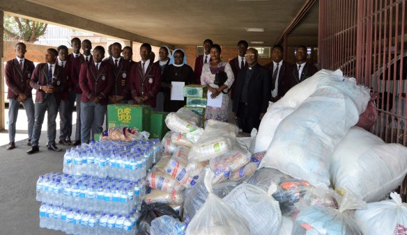 Prince Edward High School Interact Club hands over goods donated to St. Charles Luanga to ZCBC Secretary General, Fr. Fradereck Chiromba