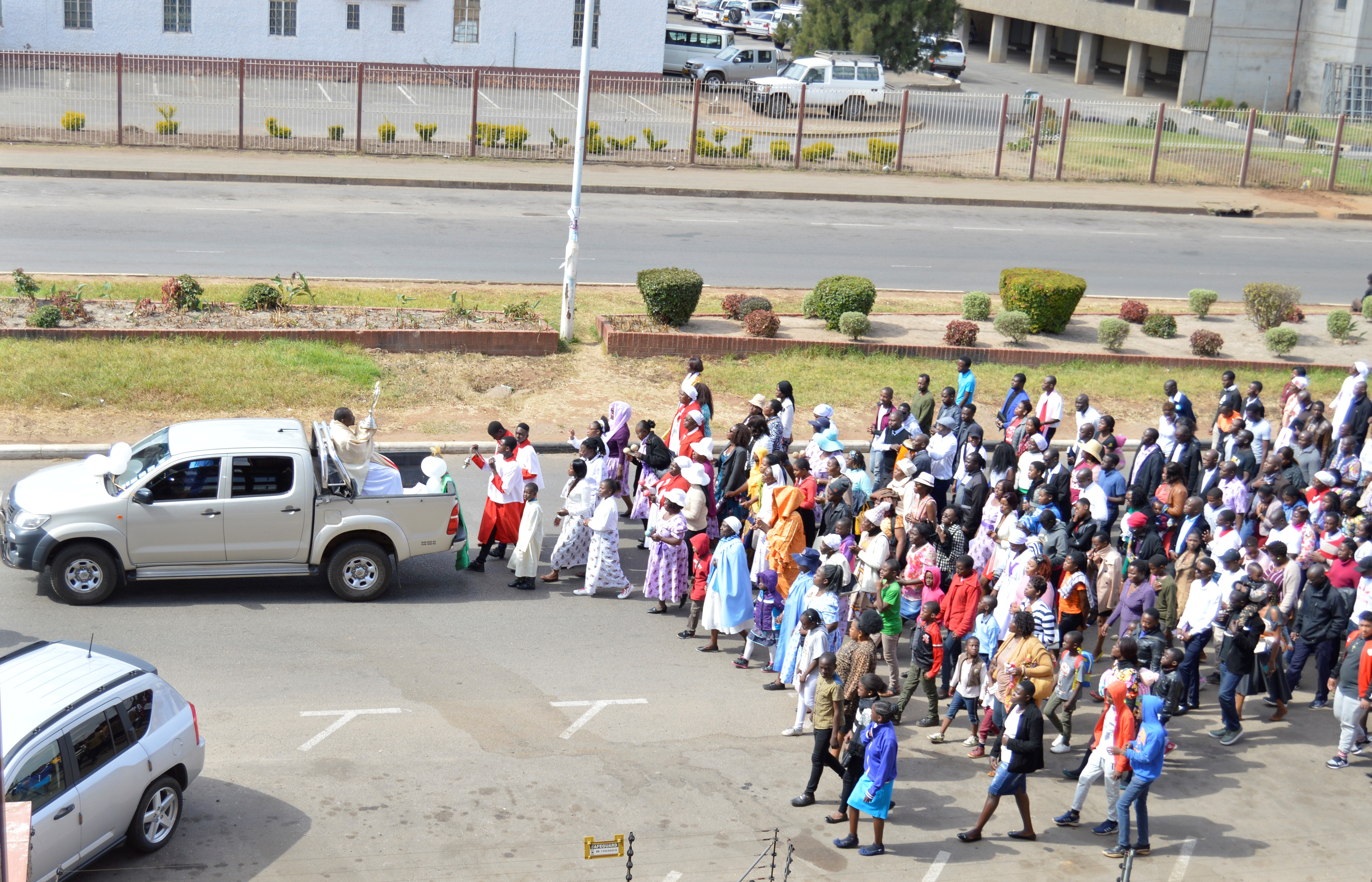 Fr. Kennedy Muguti lifts a monstrance with the blessed sacrament in a procession along Simon Muzenda Street in Harare.