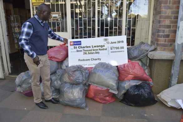 Justice Makura places the cheque on a pile of goods donated by RedCom.