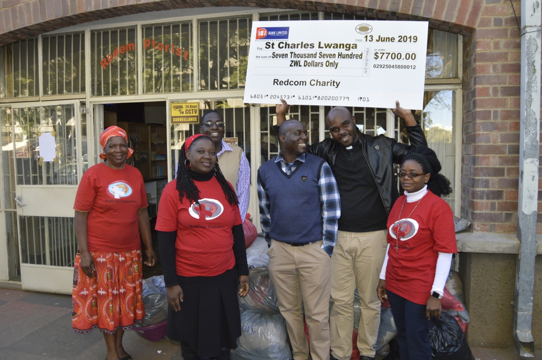 RedCom Coordinator, Mrs. Dorothy Zakeyo, Mrs. Mombo, Br. Kenneth Temba, Mr. Justice Makura, Fr. Talent Muhomba lifting the cheque and Mrs. Dhlamini pose for a picture after the presentation of goods meant for the victims of