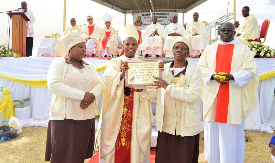 Archbishop Alex Thomas presents a plaque to honour Mrs. Anna Mugadza for her stelling work in the Archdiocese as a catechist for 45 years.