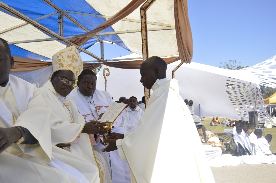Fr. Kudakwashe Chidhe receives a chalice of wine and a host from Bishop Bhasera.