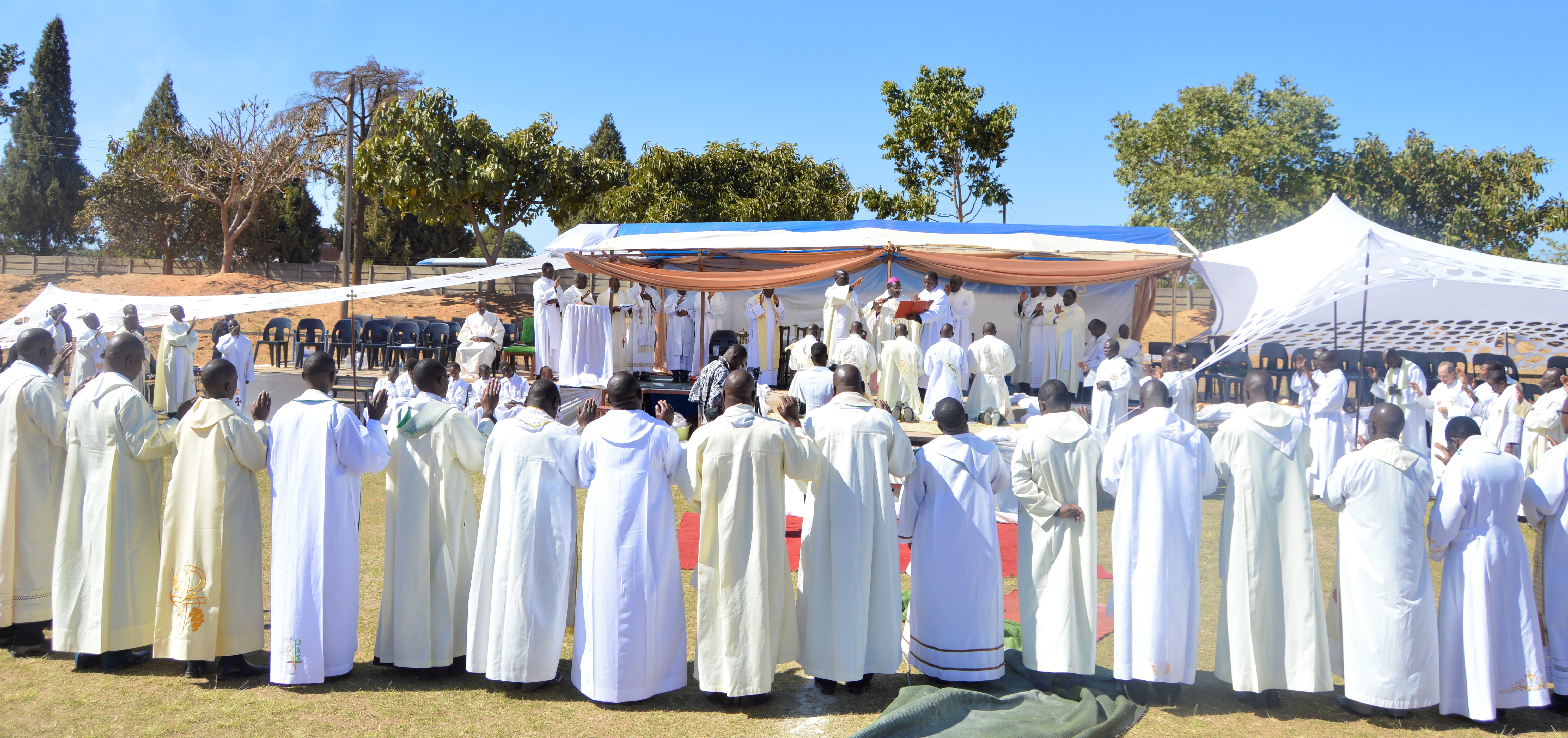 Priests encircle the ordinands while Bishop Bhasera prays over them.