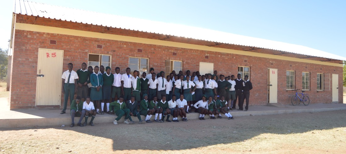 Students pose for a picture at one of the blocks at Batsirai Secondary School.